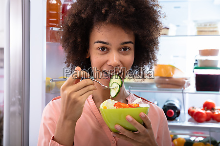 happy woman eating salad in bowl