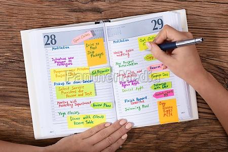 geschaeftsfrau schreibt zeitplan in diary mit