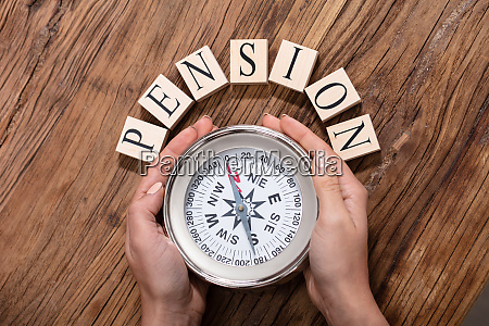 hand holding compass surrounded with pension