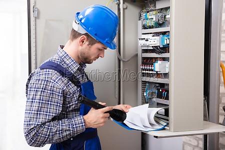 techniker holding taschenlampe und folder datei