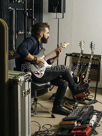 playing his electric guitar in the