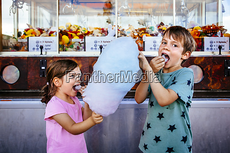 kinder essen zuckerwatte im karneval