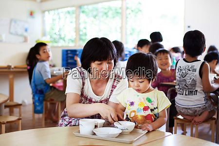 female teacher sitting at table in