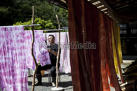 japanese man sitting outside a textile