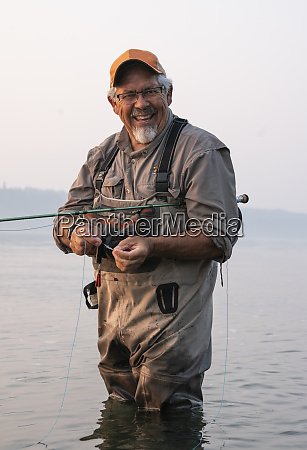 caucasian senior male tying a fly