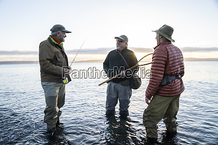 two fly fisherman talk with their