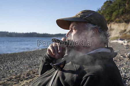 a fly fisherman enjoys a cigar