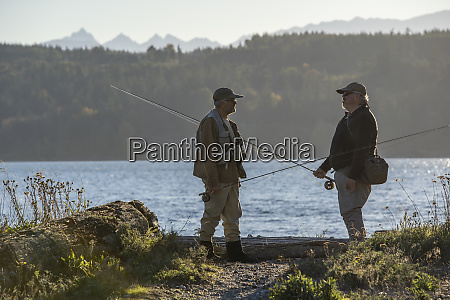 two fly fisherman talk over techniques