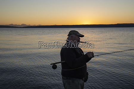 a caucasian senior fly fisherman enjoys