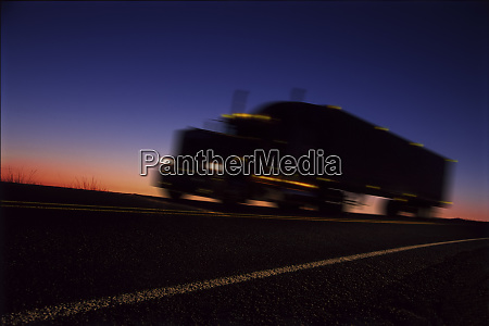 a sleeper truck silhouetted on road