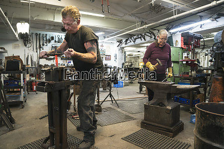 caucasian male and female blacksmiths metalworkers