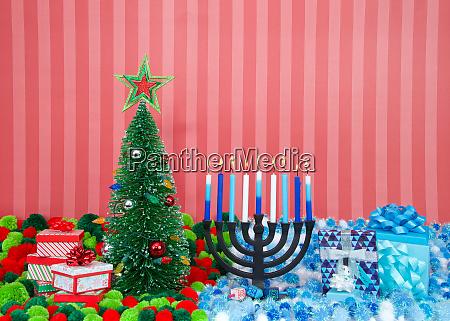 weihnachtsbaum mit geschenken neben hanukka menorah