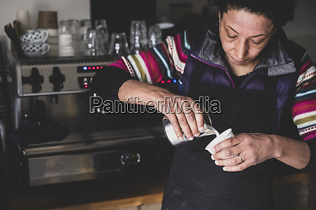 woman behind espresso machine pouring hot
