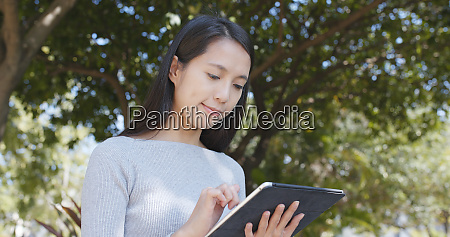 woman using tablet computer over green