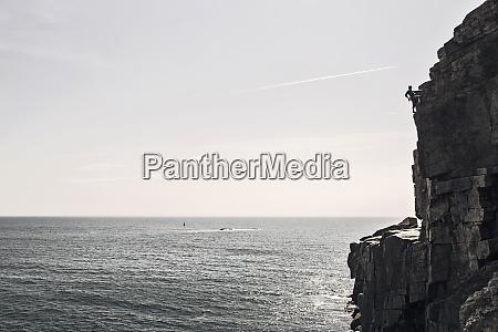 man climbing on otter cliffs overlooking