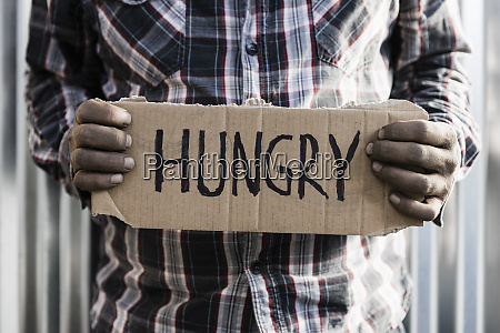 homeless man holding hungry sign