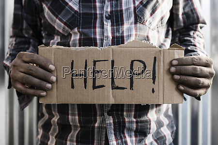 homeless man holding help sign