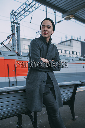 young man waiting on railroad station