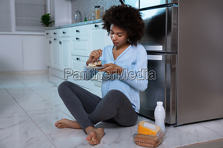 pregnant woman eating piece of cake