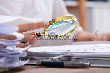 woman holding magnifying glass over invoice