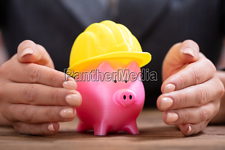 person protecting piggy bank with yellow