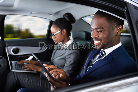 two businesspeople sitting inside car using
