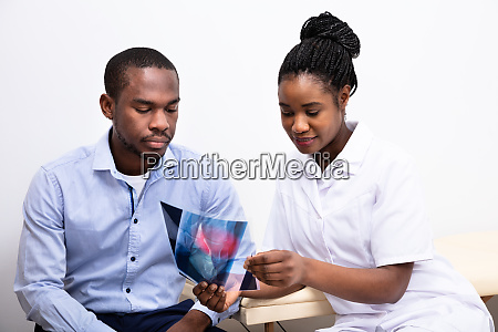 doctor showing feet x ray to