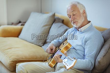 active senior man playing guitar on