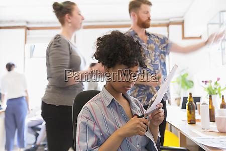 creative female designer cutting photograph in