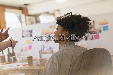 creative female designer listening to colleague