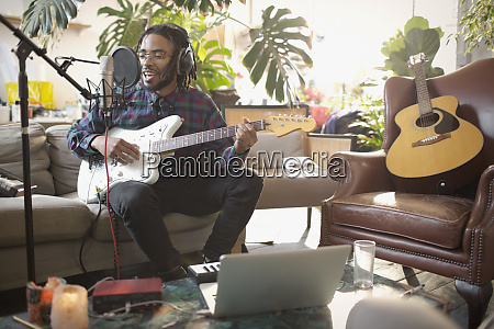 young male musician recording music playing
