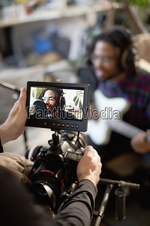 videographer filming young male musician singing