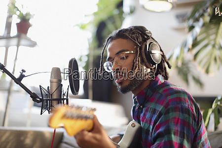 young man recording music playing guitar