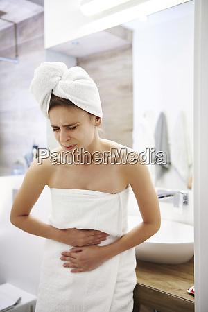 junge frau im badezimmer leidet an