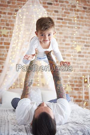 father lifting up son at christmas