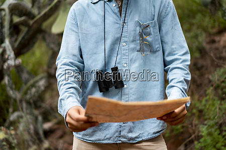 young man standing in nature looking