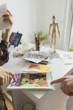 frauenhaende zeigen auf malerei am schreibtisch