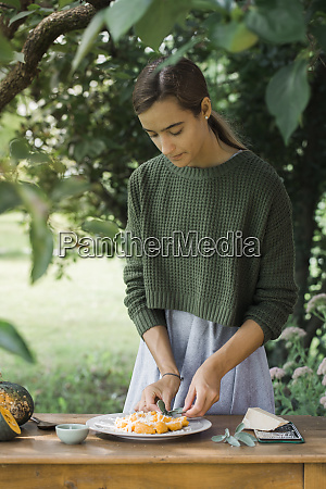 young woman garnishing homemade pumpkin gnocchi