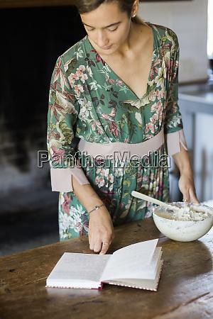 young woman preparing cake dough looking