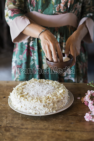 young woman garnishing home baked cake