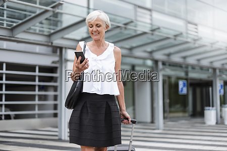smiling senior woman with baggage looking