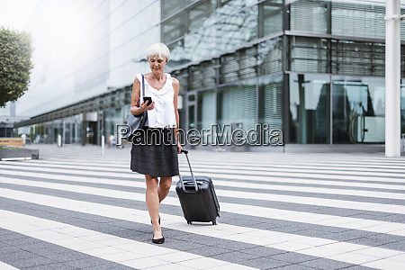 smiling senior woman with baggage on