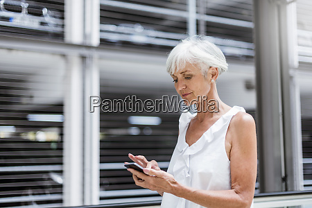 senior woman using cell phone outdoors