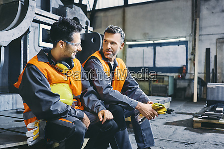 two men wearing protective workwear talking