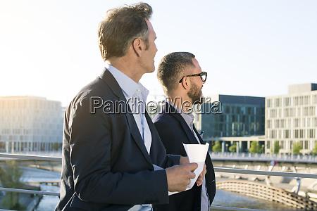 two businessmen on a bridge in