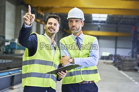 zwei manager die schutzkleidung tragen sprechen