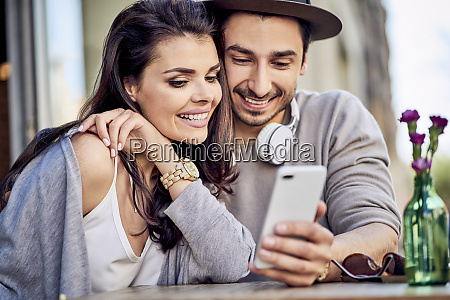 happy young couple using cell phone