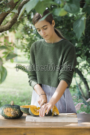 young woman cutting pumpkin for preparing