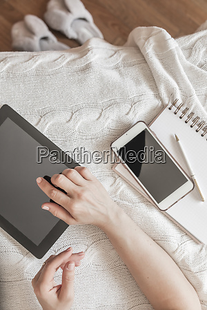 womans hand using digital tablet at