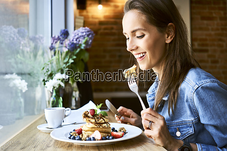smiling young woman eating pancakes in